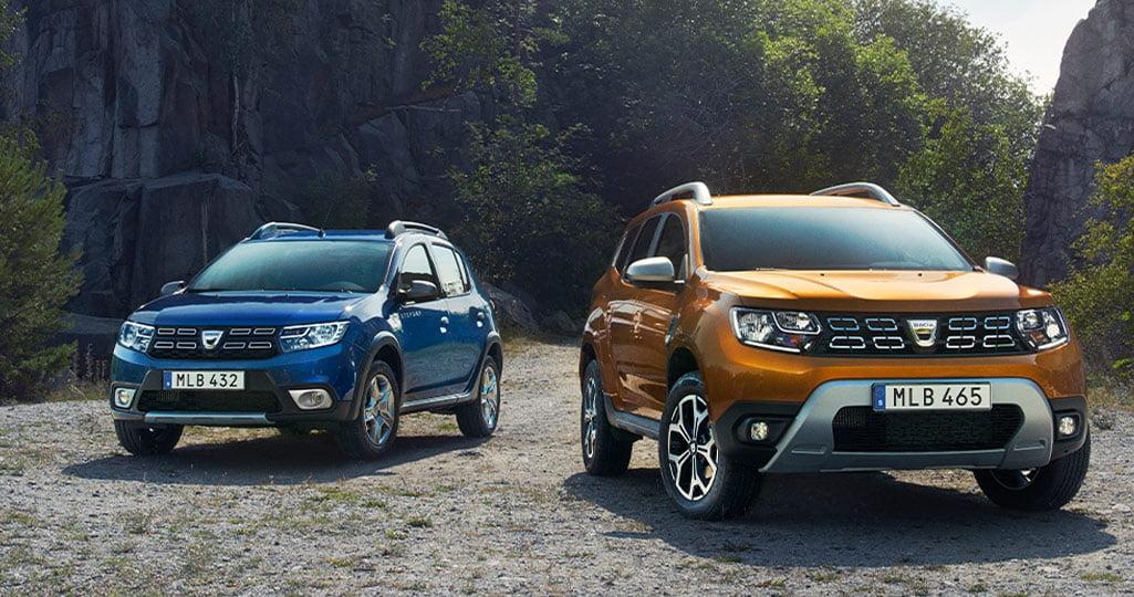Två bilar från Dacia på en grusplan i skogen. Den ena är en bensinbil och det andra är en dieselbil.