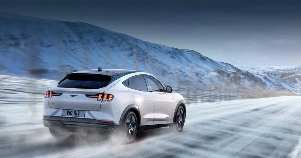 Mustang Mach-E elbil som kör i ett snöigt landskap.