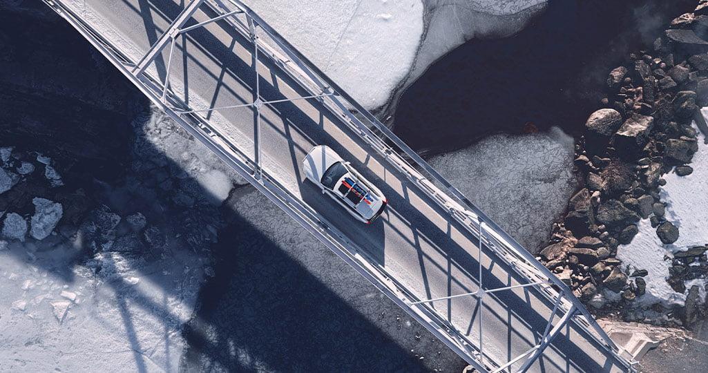 Hur gör man för att maximera räckvidden på en elbil? Elbil med skidor på taket som kör över en bro i vinterlandskap.