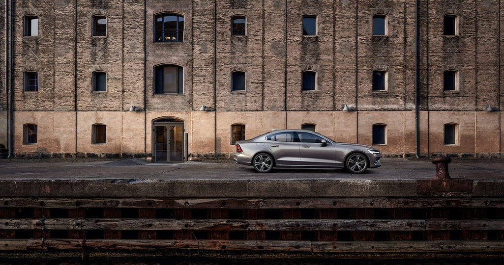 Volvo S60 silver står parkerad vid en industrilokal