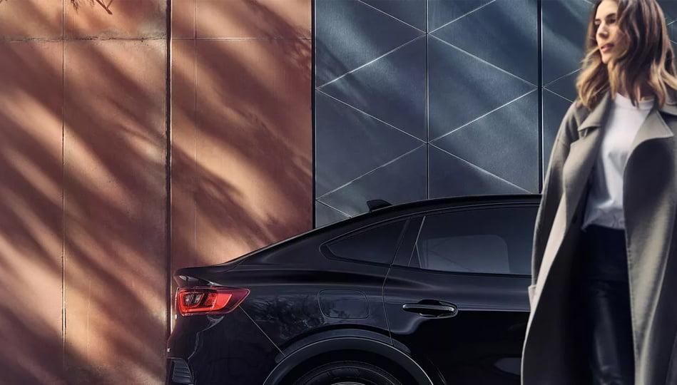 En svart Renault Arkana parkerad utanför hus, en kvinna syns i förgrunden