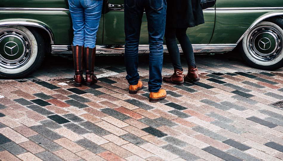Tre personer som står och tittar på en bil