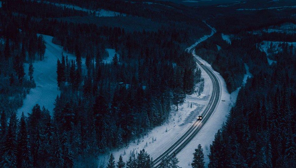 Bil som kör i mörkret längs en vinterväg