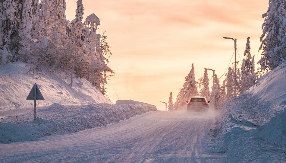 Bil som kör upp för en backe en solig vintermorgon